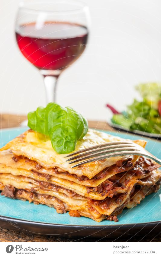 Lasagne on a blue plate Meat Cheese Nutrition Lunch Dinner Crockery Plate Restaurant Gastronomy Wood Fresh Blue Portion Baking Specialities Parmesan Wheat