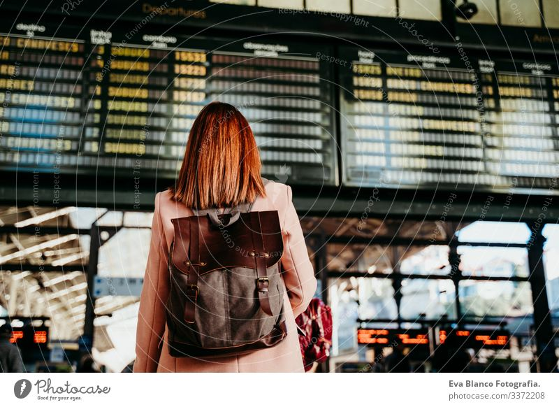 young woman at train station looking at destination board. Travel and public transport concept screen travel backpack back view caucasian europe railway waiting