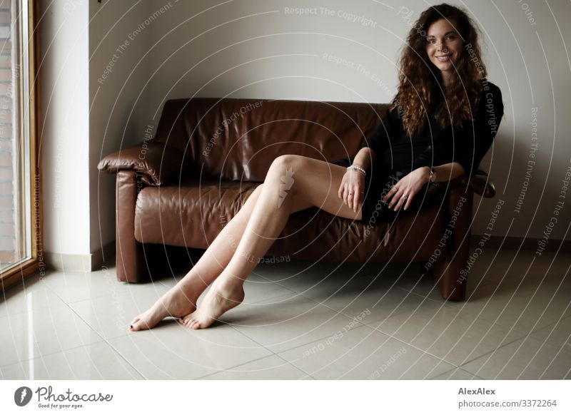 Portrait of a young, tall woman sitting barefoot on a brown leather couch and smiling Style Joy already Life Well-being Flat (apartment) Sofa Young woman