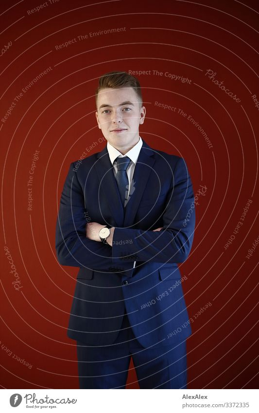 Young man in suit in front of red wall Lifestyle Luxury Style Joy pretty Well-being Office Workshop Youth (Young adults) 18 - 30 years Adults Suit Tie Blonde