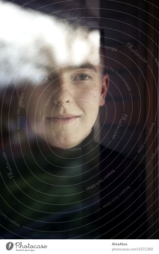 Portrait of a young man behind windowpane Elegant Style pretty Well-being Flat (apartment) Young man Youth (Young adults) Face 18 - 30 years Adults