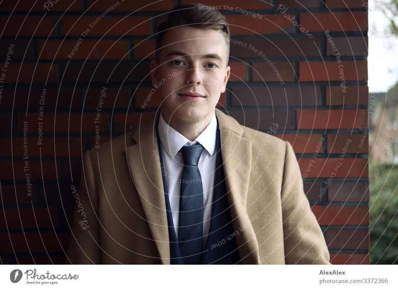 Portrait of a young man Lifestyle Style Joy pretty Brick wall Balcony Young man Youth (Young adults) 18 - 30 years Adults Beautiful weather Suit Coat Blonde