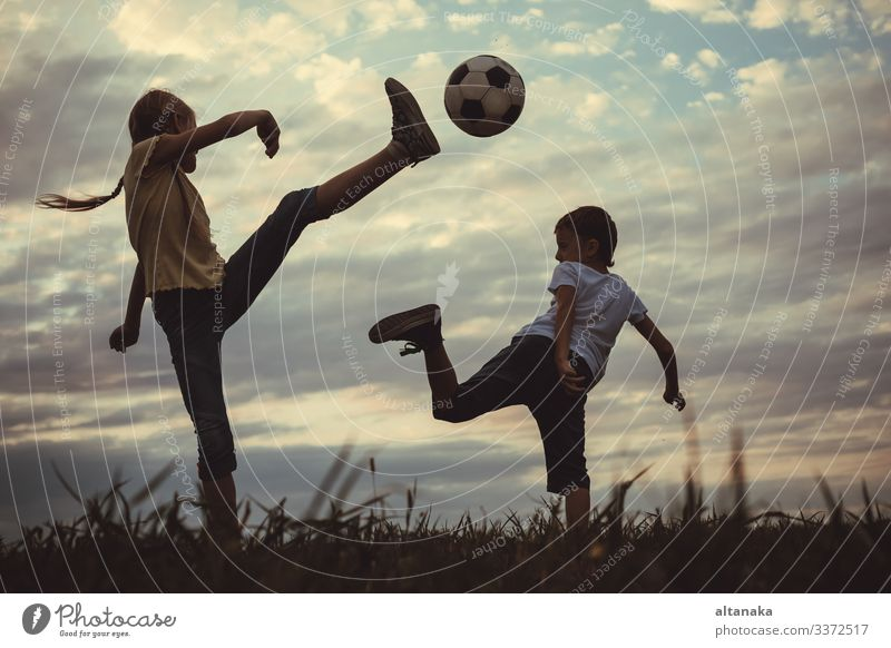 Happy young little boy and girl playing in the field with soccer ball. Kids having fun outdoors. Concept of sport. Lifestyle Joy Leisure and hobbies Playing