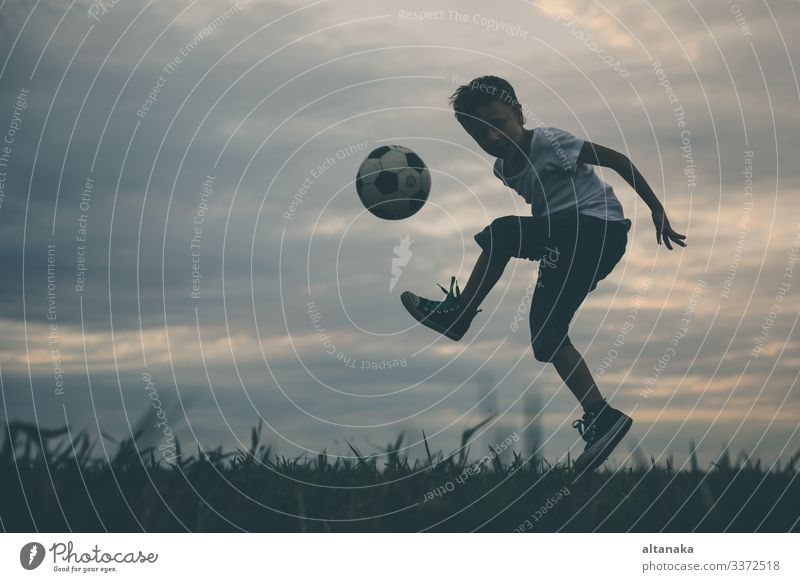 Young little boy playing in the field with soccer ball. Lifestyle Joy Happy Relaxation Leisure and hobbies Playing Summer Sports Soccer Child Human being