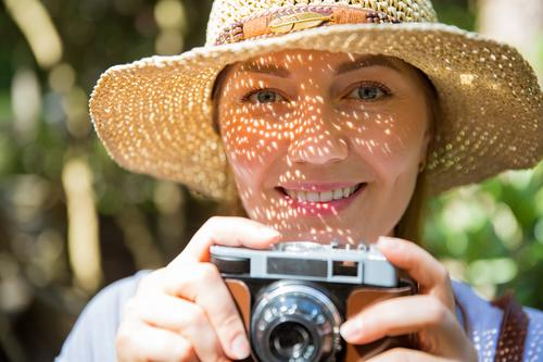 Close-up portrait of a beautiful woman in straw hat travelig in tropic forest, taking photos on retro camera. Light shadows through the cut-out detailed brim on face. Tourist with backpack.