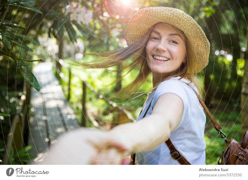 Beautiful woman in straw hat travel in tropic forest, walking along wooden path, leading her partner. Tourist with backpack. Follow me concept. active adventure