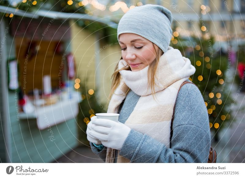 Young woman in Christmas market drinking cup of hot chocolate with marshmallow wearing knitted warm hat and scarf. Illuminated and decorated fair kiosks and shops on background. Helsinki, Finland