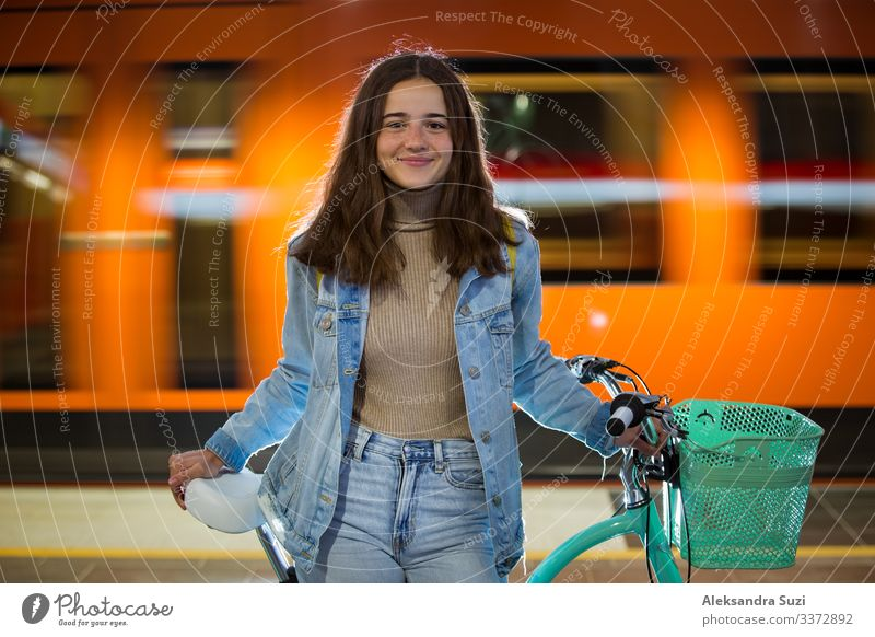 Teenager girl in jeans with yellow backpack and bike standing on metro station, waiting for train, smiling, laughing. Orange train passing by behind the girl. Futuristic subway station. Finland, Espoo