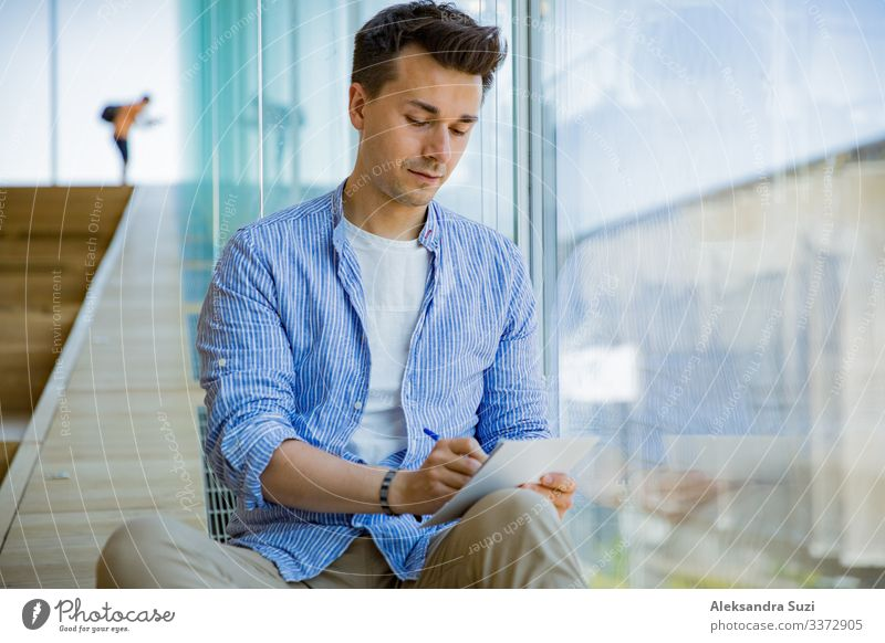 Man writing in notebook, sitting on steps at big windows, big working space. adult casual checklist concentrated concept creative creativity designer diary