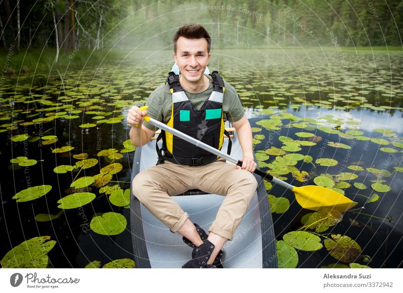 Two men in life vests canoeing in forest lake. Action Going Adventure candid Canoe Destination Discover Finland Forest Happy Lake Landscape Lifestyle Man Nature