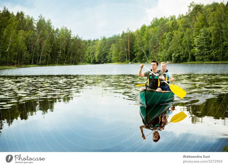 Two men in life vests canoeing in forest lake. Action Adventure candid Canoe Destination Discover Finland Forest Happy Lake Landscape Lifestyle Man Nature