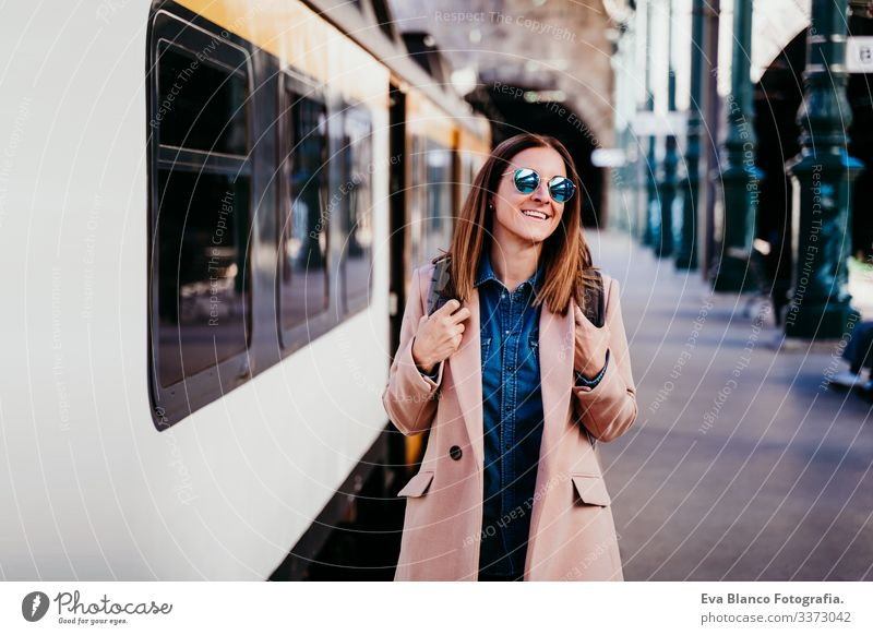 happy young woman walking at train station. Travel concept screen destination travel backpack caucasian europe railway waiting track wagon arrival long urban