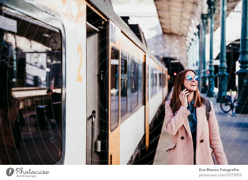 young woman at train station using mobile phone. Travel concept screen destination travel backpack caucasian europe railway waiting track wagon arrival long