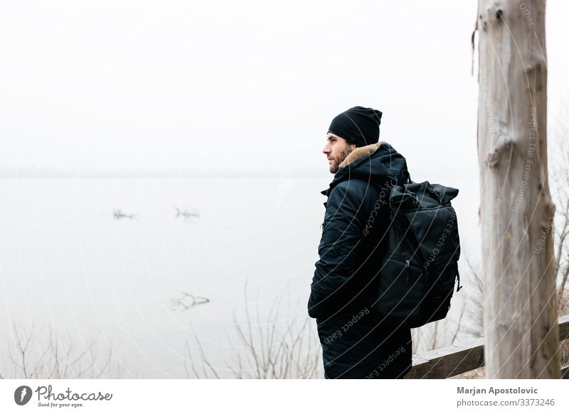 Young man standing by the river in winter morning active activity adult adventure alone backpack casual coast cold countryside day enjoy explorer foggy frost