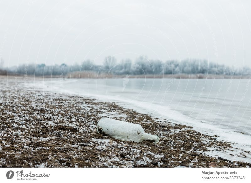 Glass bottle by the river in winter morning abandoned blue close-up coast cold country day decay dirt dirty dissolving dump ecology environment europe foggy