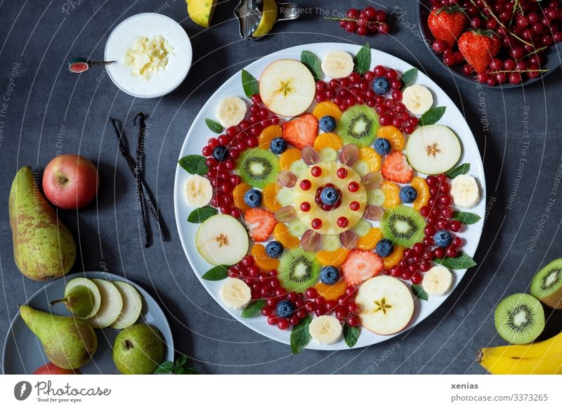 Delicious mixed fruit salad arranged as a pattern on a white plate Fruit salad Food apples Vanilla pod Pear Kiwifruit Lemon Bunch of grapes Lemon Balm Cream