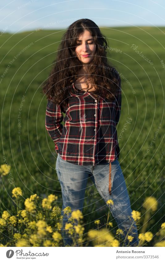 Pretty woman in spring portrait Lifestyle Human being Woman Adults Flower Meadow Shirt Jeans Long-haired Stand spanish Sunset plaid shirt people 1 Person 40s