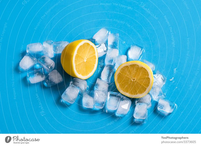 Fresh lemon sliced in half on ice cubes. Citrus fruits Fruit Cold drink Healthy Eating Blue background citrus fruit colorful Copy Space cut in half food