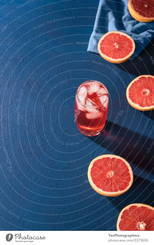 Grapefruit drink and slices citrus fruits. Grapefruit halves Fruit Beverage Cold drink Lemonade Juice Glass Fresh Juicy Colour Blue background blue table
