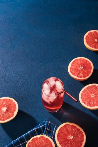 Organic grapefruit slices and cold drink. Lemonade Fruit Beverage Cold drink Juice Glass Fresh Juicy Colour Blue background blue table Citrus fruits
