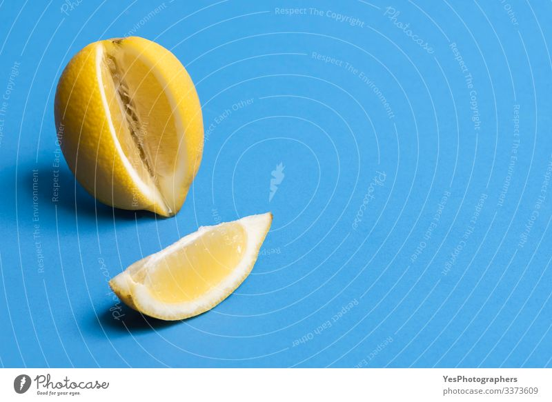 Ripe lemon and one slice of lemon. Citrus fruits. Fresh fruits Fruit Healthy Eating Blue background citrus fruit colorful Copy Space food fresh fruit