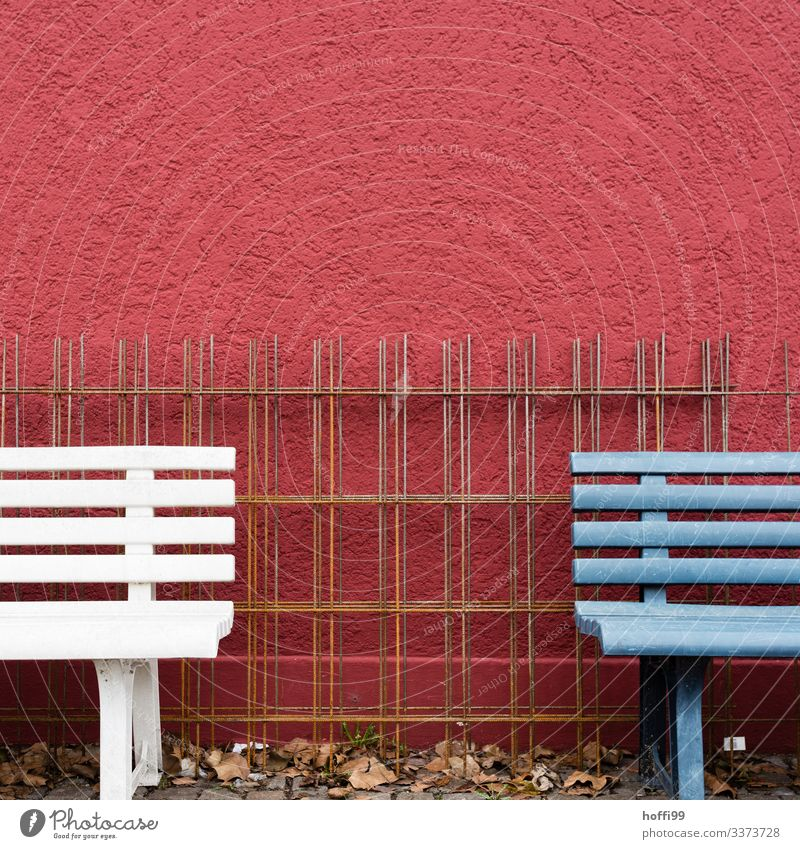 Fragment of two benches with steel grid in front of red wall Bench fragments reinforcement steel armouring corrosion Reinforcement mesh reinforcing bars
