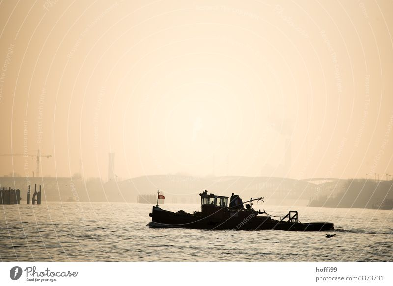 Silhouette of a small tugboat in Hamburg harbour with early morning fog and rising sun Water Sky Sunrise Sunset Sunlight Autumn Bad weather Fog Coast River bank