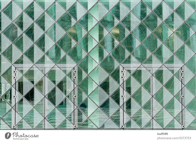 green reflecting transparent facade with doors and snow Glas facade reflection Green square Pattern square structure urban Modern Atchitecture