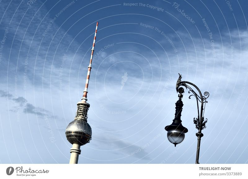 Berlin television tower at Alexanderplatz and street lamp in historical style parallel and reflecting the sunlight against the blue sky with partly light cloud cover