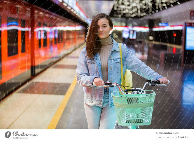 Teenager girl with backpack and bike standing on metro station holding smart phone in hand, scrolling and texting, smiling and laughing. Futuristic bright subway station. Finland, Espoo