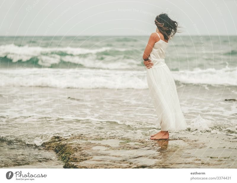 Back view of Pensive Young woman on the beach young woman beautiful elegant elegance dream dreaming dreams dress fashion freedom fun glamor independence joy