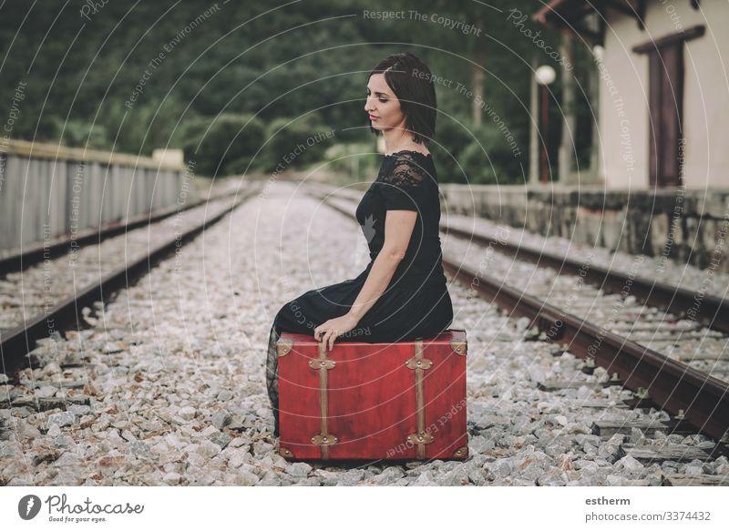 young woman sitting on a suitcase on railway station beautiful elegant elegance romantic fragility love femininity dress nostalgia freedom beauty outdoors
