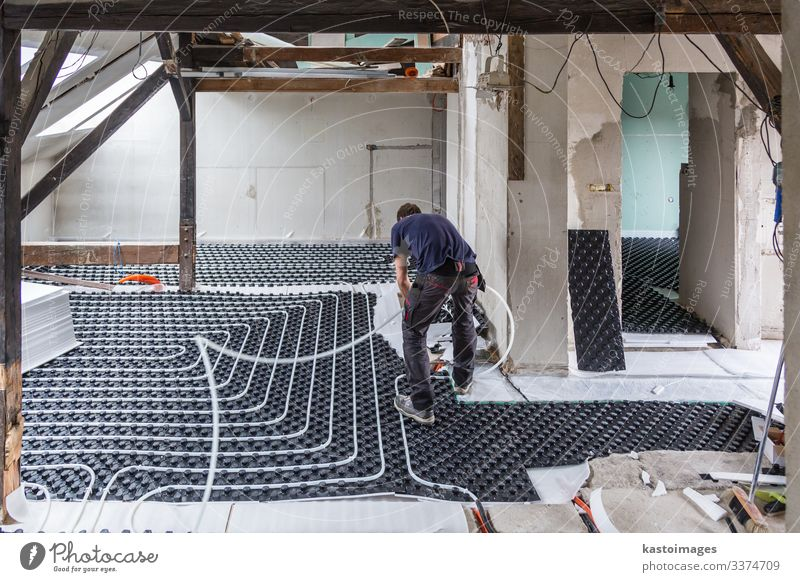 Pipe fitter mounting underfloor heating. House (Residential Structure) Life Work and employment Places Industry Climate Ground Plastic Under Material Story