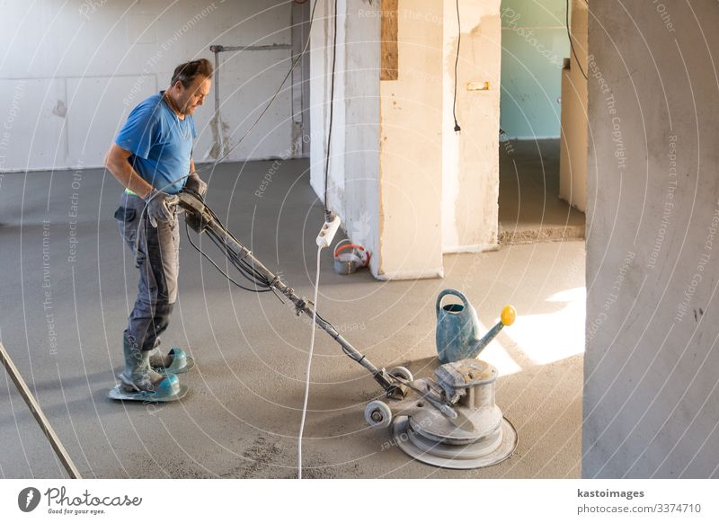 Laborer polishing sand and cement screed floor. Work and employment Craftsperson Human being Man Adults Sand Building Concrete Cement construction Story float