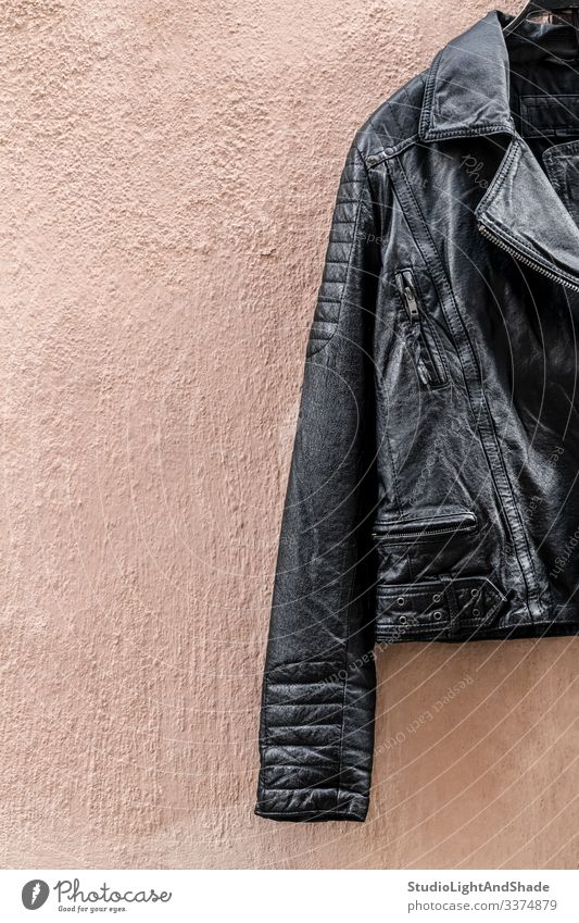 Black leather jacket on pink wall black zipper pocket fashion style stylish shiny cool rock rocker metal heavy metal clothing clothes apparel outfit fetish wear