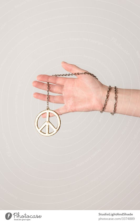 Female hand holding peace sign pacific arm fingers female girl woman young hippie youth gold golden gray grey pink white chain bracelet jewelry metal metallic
