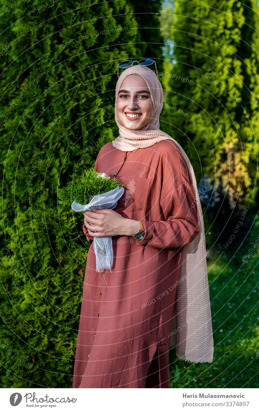 Muslim woman in hijab smiling  with flowers bouquet muslim religion smile portrait beautiful beige bright cheerful close up clothing confident dress elegant