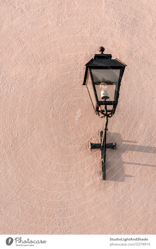 Streetlight on a textured pink wall streetlight streetlamp lantern electricity painted stone background surface dusty pink pastel metal old ancient concrete