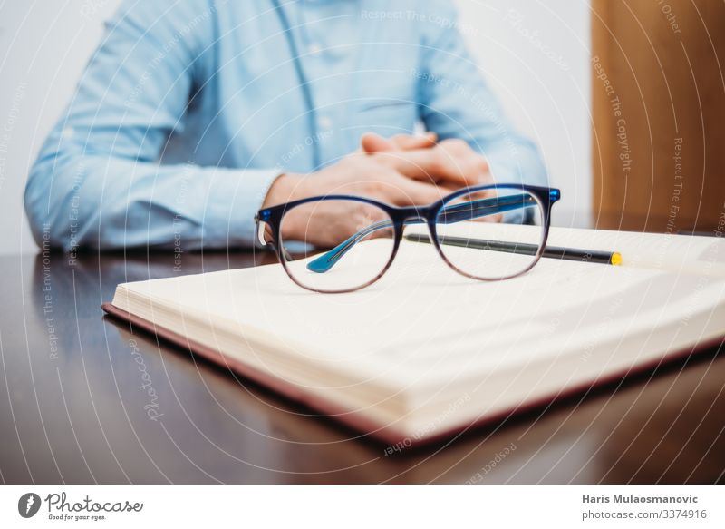 man hands sitting at the desk, with book and glasses study, working in the office Table Education Student Study Work and employment Profession Economy