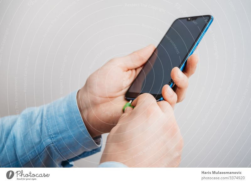 Man hands holding smartphone with headphone jack Telephone Technology Entertainment electronics Telecommunications Internet Hand Cool (slang) Blue White