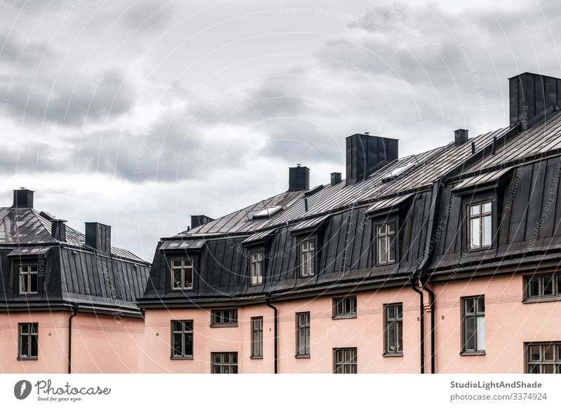 Pastel colored buildings with black roofs house houses windows rooftop Europe European Stockholm Sweden Swedish Scandinavia Scandinavian attic urban city town