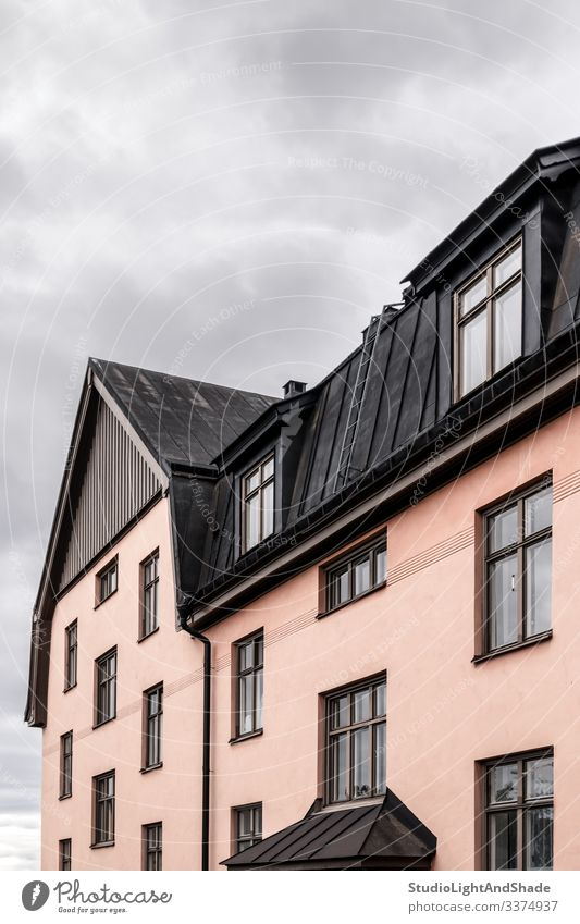 Pastel colored building with black roof house windows rooftop Europe European Stockholm Sweden Swedish Scandinavia Scandinavian attic urban city town pastel