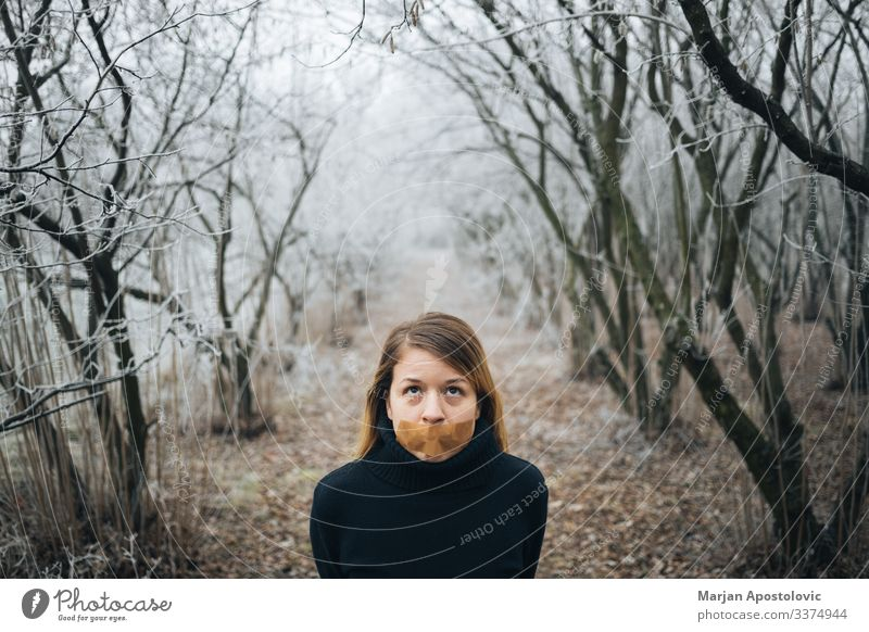 Woman with tape on her mouth in cold winter forest adult anxiety behavior blond caucasian censorship civil concepts depression despair distraught emotional