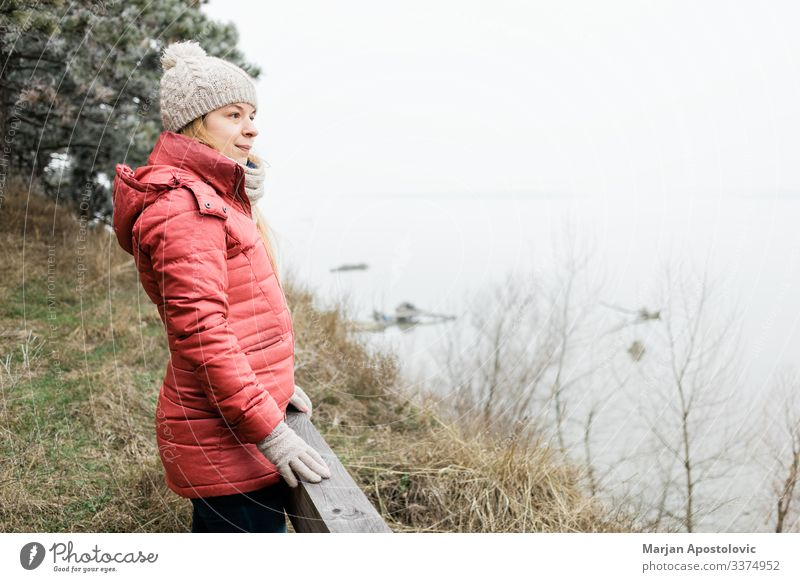 Young woman standing by the river in winter morning active adult adventure alone beautiful cap casual caucasian coast cold enjoying female free freedom frost