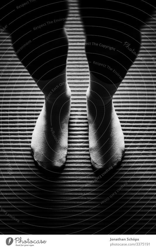 Woman standing attentively with socks on yoga mat Abstract black background Legs dark fashion Fitness feet sleeping mat Leggings Minimal black minimalism Shadow