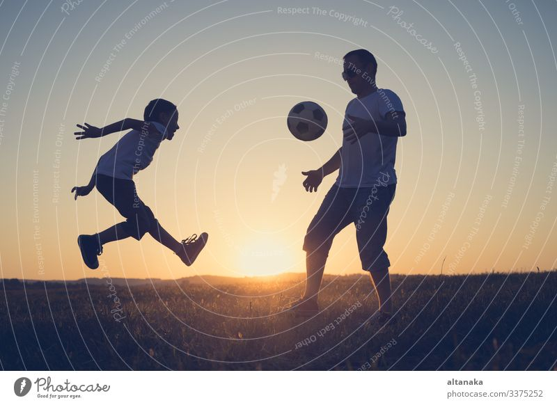 Father and young little boy playing in the field with soccer ball. Concept of sport. Lifestyle Joy Happy Leisure and hobbies Playing Summer Sports Soccer Child