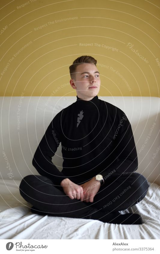 Young man sitting cross-legged on bed in front of yellow wall Lifestyle Style Joy Beautiful Well-being Bed Room Bedroom Youth (Young adults) 18 - 30 years