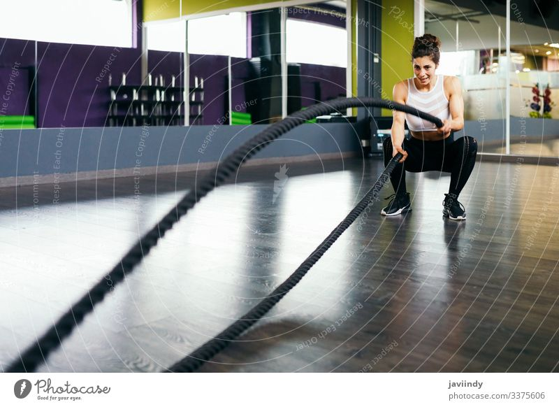 Young and athletic woman using training ropes in a gym. fitness workout female sportswoman athlete active young muscular exercise adult strength body strong