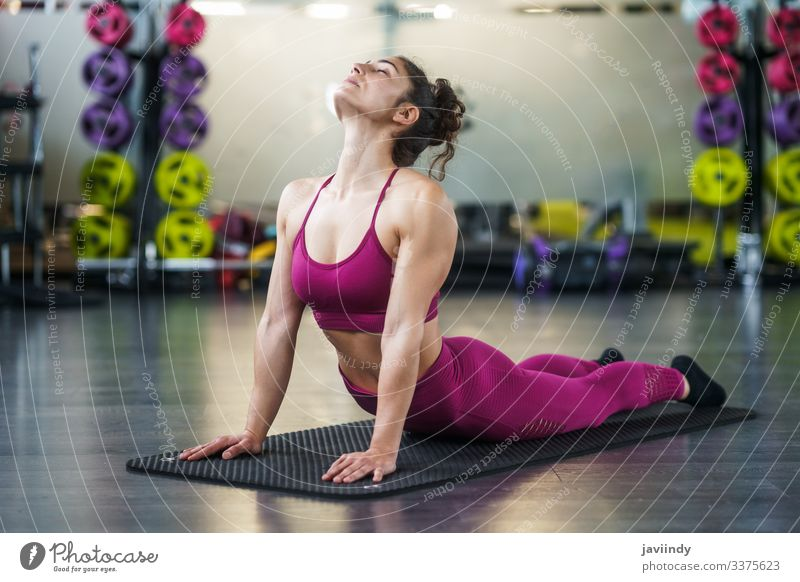 Young woman Doing Stretching Exercises on a yoga mat stretching back gym body fit leg girl sitting healthy fitness exercise lifestyle training workout female