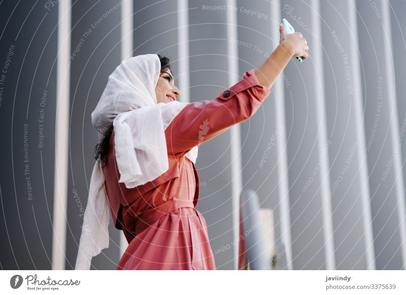Arab Woman with hijab taking selfie with smartphone woman arab muslim young photograph scarf beautiful urban city lifestyle happy street culture copyspace